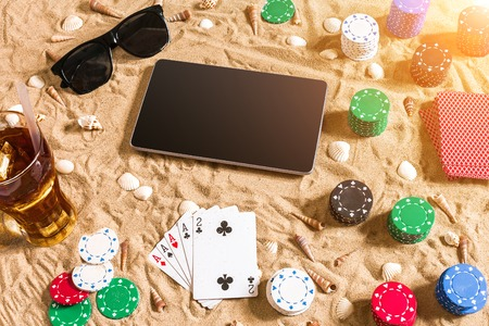 computer club: Online poker game on the beach with digital tablet and stacks of chips. Top view. Copy space. Flat lay. Sun flare