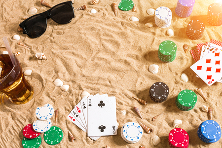 Beachpoker. Chips and cards on the sand. Around the seashells, sunglasses and cold drink in a glass. Top view