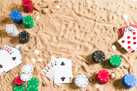 Beachpoker. Chips and cards on the sand with seashells. Top view