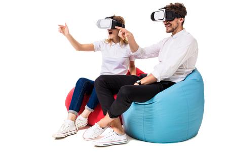 Opgewekt jong paar die virtuele die werkelijkheid ervaren op beanbags wordt gezeten op witte achtergrond worden geïsoleerd
