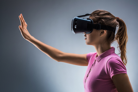Young woman wearing virtual reality headset in studio. Emotions. Side view