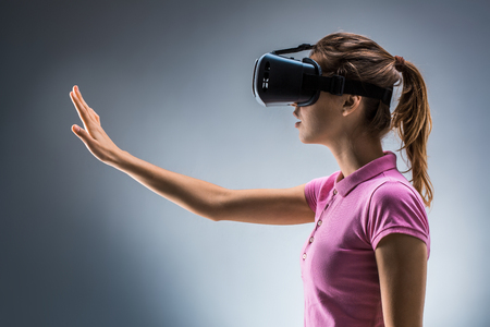 virtual reality simulator: Young woman wearing virtual reality headset in studio. Emotions. Side view