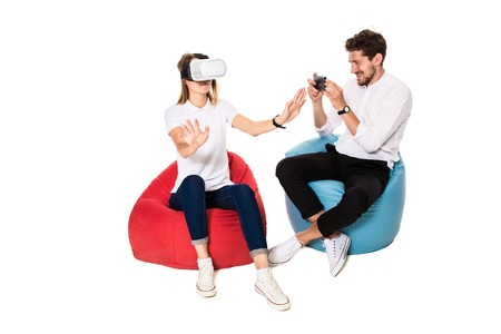 Smiling friends experiencing virtual reality glasses seated on beanbags isolated on white background.