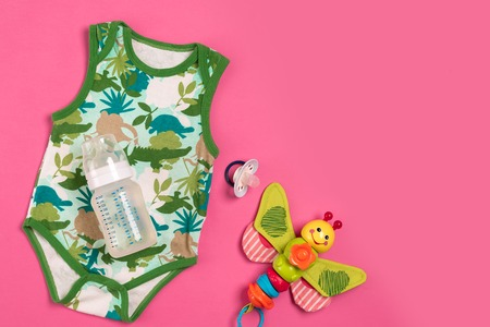 White and green bodysuit and bottle on pink background. Things for babies. Top view. Copy space. Flat lay. Still life