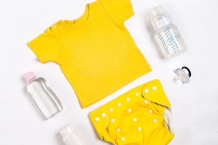 Yellow childrens costume, bottle and orthodontic pacifier on a white background. Top view. Copy space. Flat lay. Still life