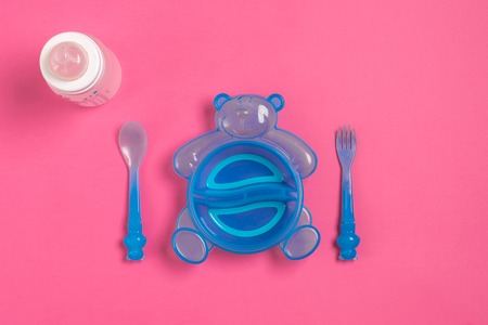 plato del buen comer: Baby bottle and blue plate with spoon and fork isolated on pink. Top view. Copy space. Flat lay
