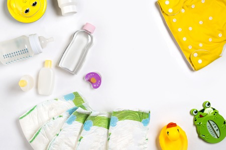Babies goods diaper, baby powder, cream, shampoo, oil on white background with copy space. Top view or flat lay. Maternity concept Stok Fotoğraf - 82317961