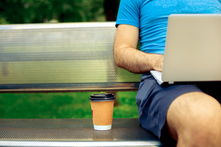 Freelance work. Casual dressed man sitting at wooden beanch inside garden working on computer.