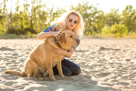 Young woman with her dog at the beach Stock Photo