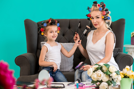 Mom and daughter in the studio on the sofa in the curlers make up and have fun