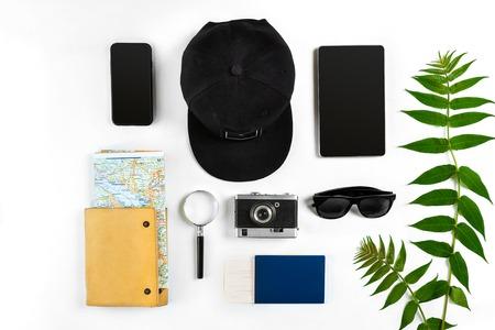 Reistoebehoren op witte achtergrond worden geplaatst: slim, paspoort, pet, blocnote, kaart, camera en zonnebril die. Bovenaanzicht. Plat leggen. Stilleven Stockfoto