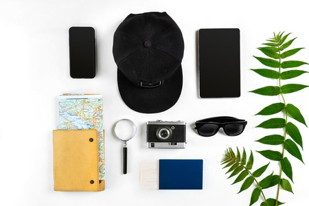 Travel accessories set on white background: smart, passport, cap, notepad, map, camera and sunglasses. Top view point. Flat lay. Still life