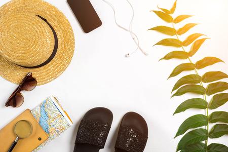 Reistoebehoren op witte achtergrond worden geplaatst: slim, hoofdtelefoons, hoed, kaart en zonnebril die. Bovenaanzicht. Plat leggen. Stilleven. Ruimte kopiëren. zonnevlam Stockfoto