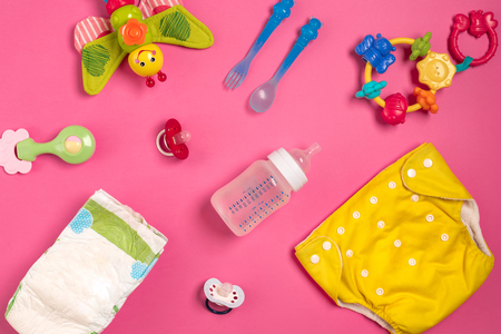 Baby care accessories and diapers on pink background. Top view Stockfoto