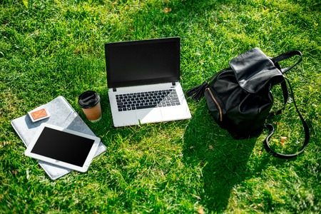 Laptop computer on green grass with coffee cup, bag and tablet in outdoor park Stock Photo