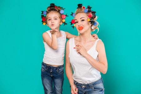 Funny family on a background of bright blue wall. Mother and her daughter girl with a paper accessories. Фото со стока