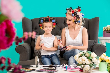 maquillage: Portrait of cute little girl and her mom doing each other makeup