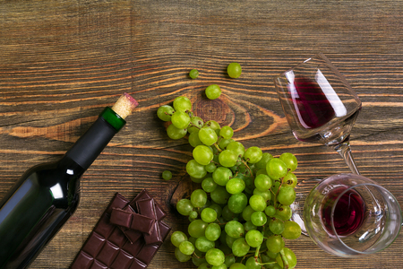 Two glasses, bottle of red wine and grape on a wooden table