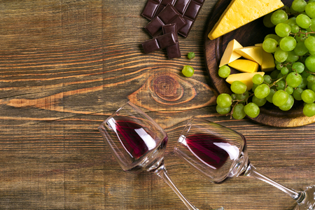Two glasses of red wine, cheese, green grapes and chocolate, top view. Copy space. Still life. Flat lay 免版税图像