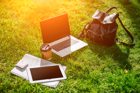 Laptop computer on green grass with coffee cup, bag and tablet in outdoor park Standard-Bild