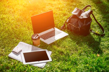 Laptop computer op groen gras met koffiekopje, tas en tablet in openluchtpark