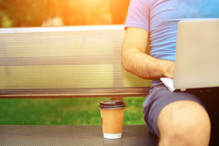 Casual dressed man sitting at wooden beanch inside garden working on computer. Stock Photo
