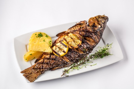 Grilled carp fish with rosemary potatoes and lemon, close up