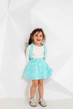 Beautiful little girl with long hair. In a lush short turquoise skirt and white T-shirt.
