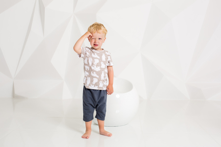 little boy in a t-shirt and shorts on a white background