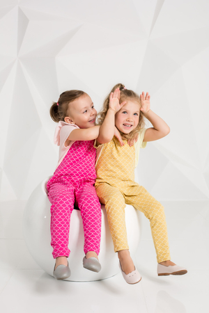 identical: Two little girlfriends in the identical overalls of different colors sitting on a chair in a studio with white walls