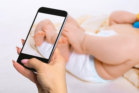 Photographing baby concept - feet of a six months old baby wearing diapers