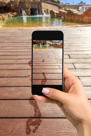 closely cropped: Closely image of female hands holding mobile phone with photo camera mode on the screen. Cropped image of footprints on the wooden floor behind it swimming pool
