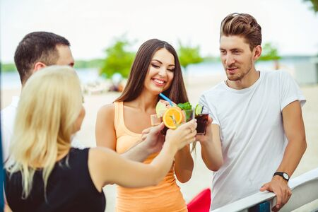 Friends having fun at the bar outdoors, drinking cocktails. Stock Photo
