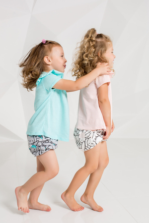 identical: Two little funny and laughing girl in the identical clothes of different colors playing in white studio