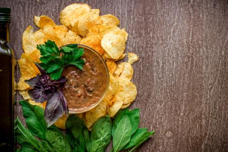 cebollines: Patatas fritas con salsa de inmersión en una mesa de madera. Comida no saludable en un fondo de madera. Vista superior. Copia espacio Endecha plana. Bodegón