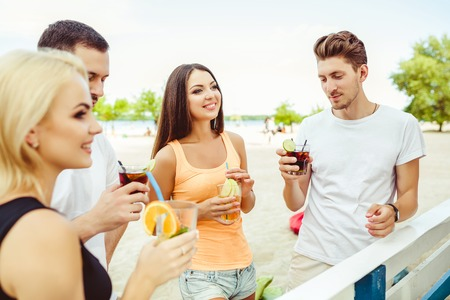 metrosexual: Friends having fun at the bar outdoors, drinking cocktails. Stock Photo