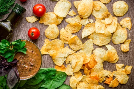 Potato chips with dipping sauce on a wooden table. Unhealthy food on a wooden background.