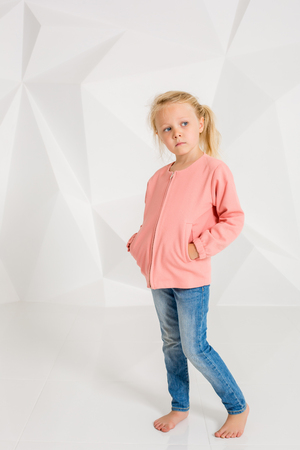Cute little girl in pink jacket and jeans, hands in pockets on white background