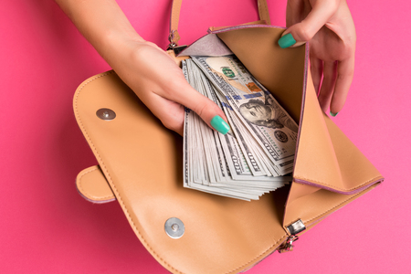 Womans hand removing money from little bag, studio shot Stock Photo