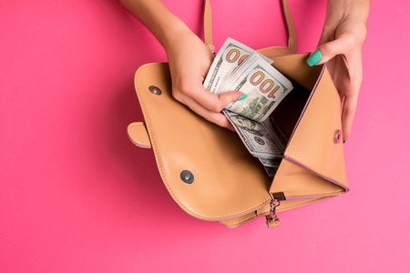 Womans hand removing money from little bag, studio shot Standard-Bild