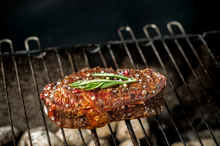 Hot spicy steak grilling on a summer barbecue over the hot coals garnished decorated with a branch of rosemary