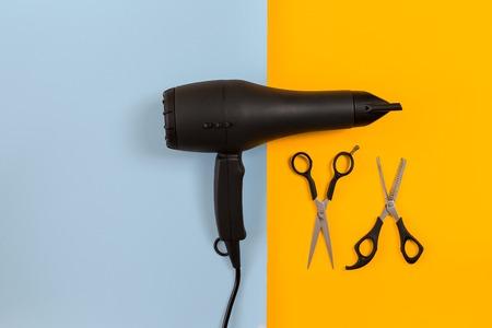 Het stileren van haar met schaar, droger en hulpmiddelen in herenkapper op blauw en geel document achtergrond hoogste meningsmodel