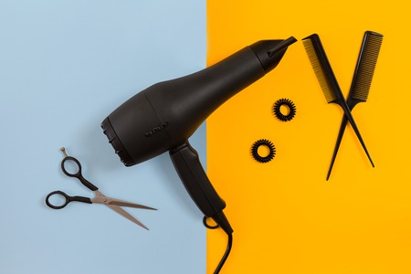 Styling hair with scissors, dryer and tools in barbershop on blue and yellow paper background top view mock-up