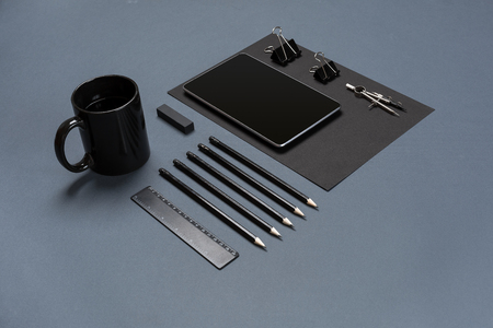 office stapler: Flat lay of blank black paper sheet, black stationery items and coffee cup on gray desktop. Mock up Stock Photo