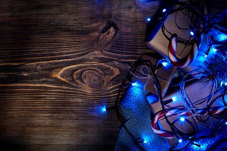Fir tree branch with christmas lights, gift box and candy canes on wooden background with copy space.