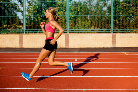 Side view beautiful young woman exercise jogging and running on athletic track on stadium Stock Photo