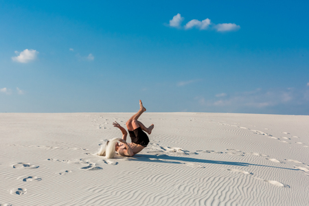 Young sporty man want doing acrobatic exercises on the sand near river Stock Photo