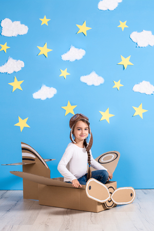 푸른 하늘과 흰 구름 배경 스튜디오에서 골 판지 비행기 놀고 작은 꿈꾸는 소녀.