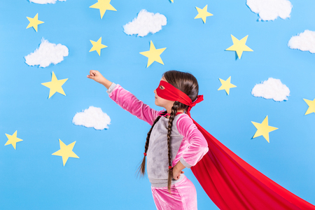 Little child plays superhero. Kid on the background of bright blue wall with white clouds and stars . Girl power concept.