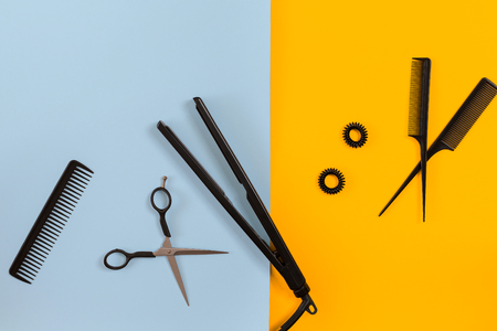 Various hair styling devices on the color blue, yellow paper background, top view